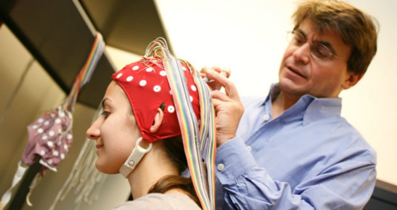Michael Ullman attaches wires and a cap to a woman's head in a lab