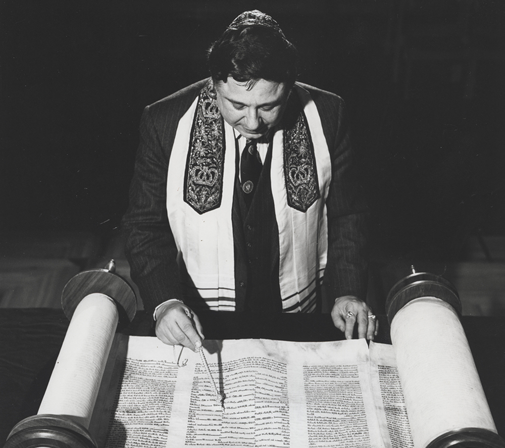 Rabbi Harold White reads over scrolls laid out on table.