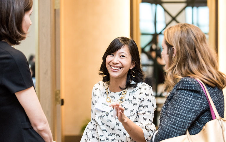 Tiffany Yu smiles into the camera while talking to two other women facing her on each side.
